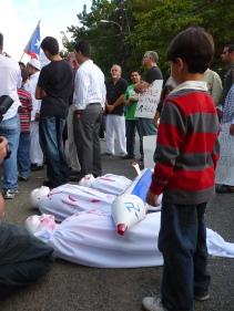 Un niño observa los cadáveres que recordaron a los hermanos palestinos caidos durante la protesta