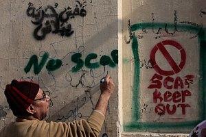 """Un hombre escribe """"No SCAF"""" en repudio al gobierno militar."""